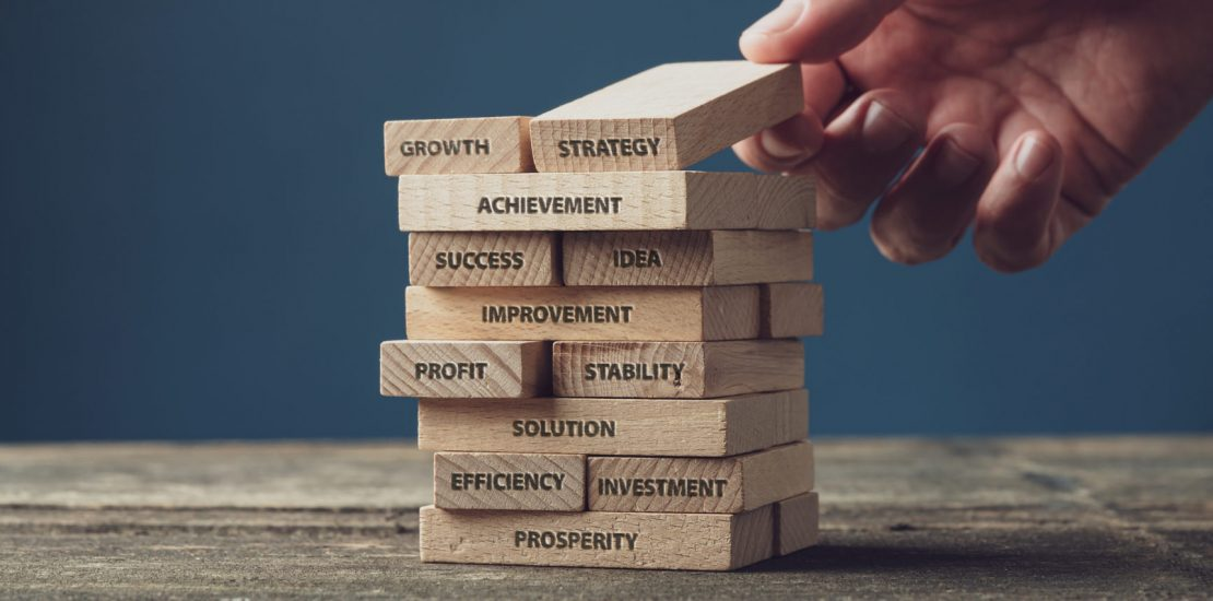 Wide view image of businessman stacking wooden pegs with words of business development and success written on them. Over blue background.